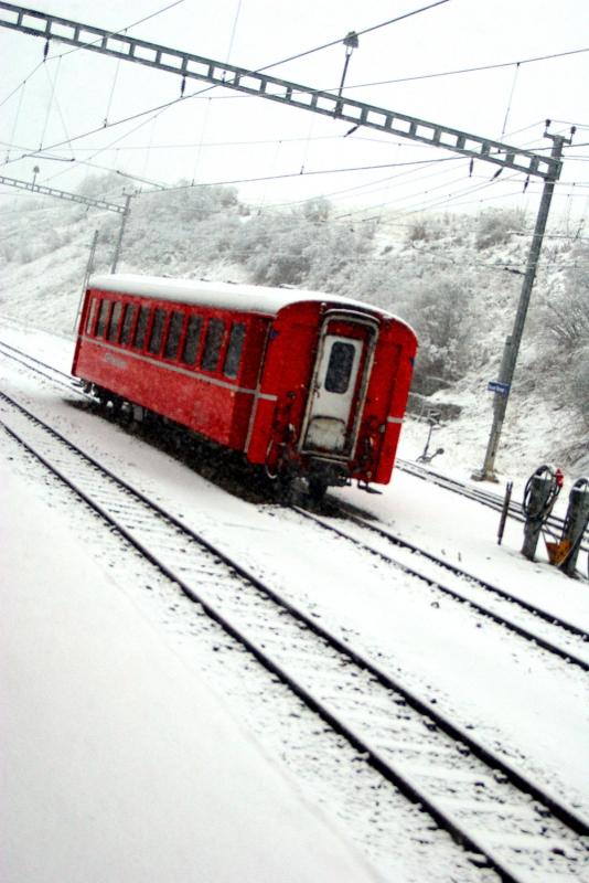 Un vagone delle ferrovie retice sotto la neve alla stazione di Scuol
