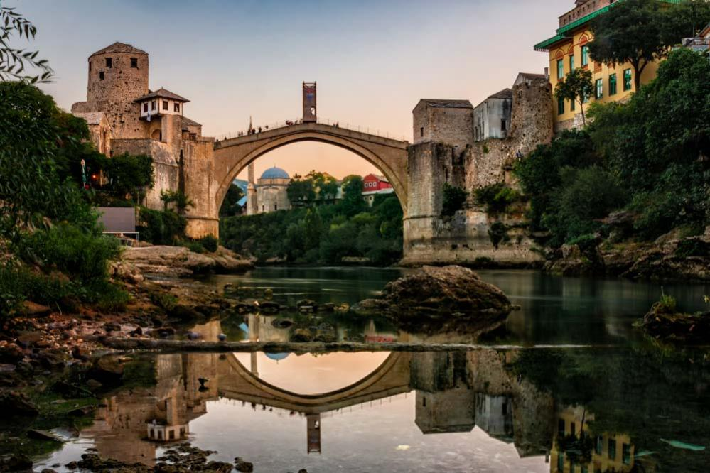 Mostar Old Bridge at sunset with view of the Neretva river and the old town.