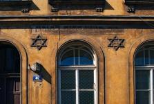 """Dall' inizio del XIX secolo questo edificio fu sede della casa per la preghiera chiamata """"Kowea Itim l'Tora"""", che signifca """"quelli che studiano regolarmente la Torah"""". Sulla facciata dell' edificio - che oggi è una casa d' abitazione - appare il nome ebraico della casa della preghiera e - nelle due stelle di Davide - le date ebraiche di fondazione (1810) e rstrutturazione (1912)"""