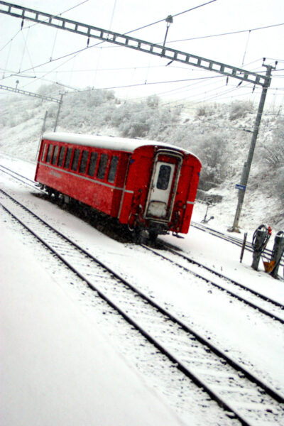 A read car under the white snow in Scuol station