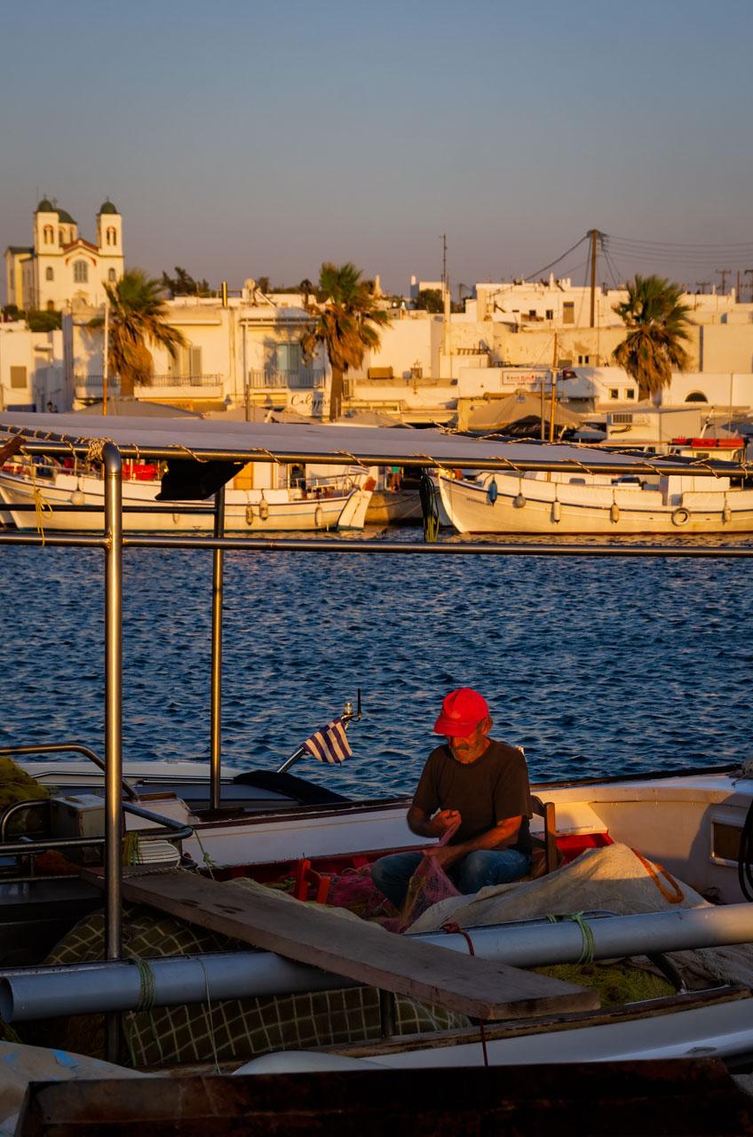 Pescatore rammenda le reti al porti di Naoussa al tramonto